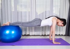 Woman doing yoga exercise with fitness ball Stock Photos