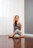 Woman doing yoga exercise on floor Stock Photography