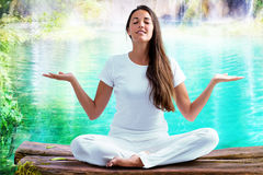 Woman doing yoga exercise at lake. Close up portrait of attractive woman dressed in white sitting in meditating position on wooden log at blue lagoon. Young Stock Photo