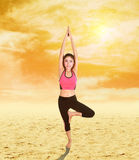 Woman doing yoga exercise on sand with sky at sunset Stock Images