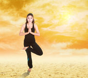 Woman doing yoga exercise on sand with sky at sunset Royalty Free Stock Photos