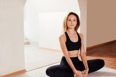 Woman doing yoga exercise, sitting in baddha konasana, butterfly pose. Young sporty woman practicing yoga at home, sitting in Butterfly exercise Royalty Free Stock Images