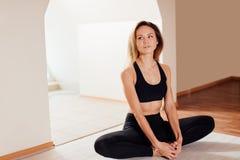Woman doing yoga exercise, sitting in baddha konasana, butterfly pose. Young sporty woman practicing yoga at home, sitting in Butterfly exercise Stock Image