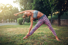 Woman doing yoga exercise in summer park Royalty Free Stock Photos