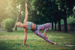 Woman doing yoga exercise in summer park Stock Photo