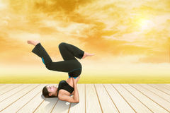 Woman doing yoga exercise on wood floor with field at sunset Stock Images
