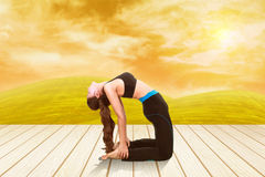 Woman doing yoga exercise on wood floor with field at sunset Stock Image