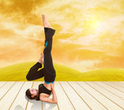 Woman doing yoga exercise on wood floor with field at sunset Royalty Free Stock Image