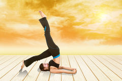 Woman doing yoga exercise on wood floor with field at sunset Royalty Free Stock Photography