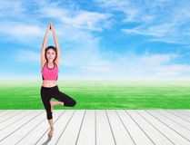 Woman doing yoga exercise on wood floor with green grass and sky Royalty Free Stock Images