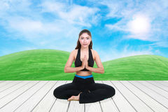 Woman doing yoga exercise on wood floor with green grass and sky. Young woman doing yoga exercise on wood floor with green grass and sky Stock Photo