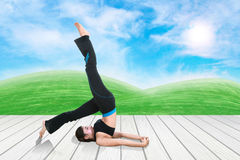 Woman doing yoga exercise on wood floor with green grass and sky. Young woman doing yoga exercise on wood floor with green grass and sky Royalty Free Stock Images