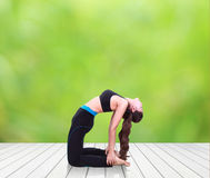 Woman doing yoga exercise on wood floor with natural blur backgr Stock Photography