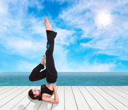 Woman doing yoga exercise on wood floor with sea and sky Stock Photos