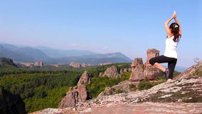 Woman doing yoga exercises on Belogradchik rocks, admiring the Belogradchik valley stock footage