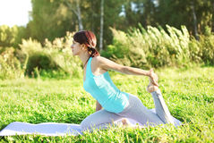 Woman doing yoga exercises on grass in summer day Royalty Free Stock Images