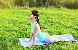 Woman doing yoga exercises on grass in summer Royalty Free Stock Photography