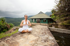 Woman is doing yoga exercises in mountains Stock Photo