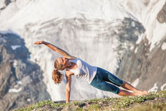 Woman is doing yoga exercises in mountains Royalty Free Stock Images