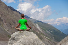 Woman is doing yoga exercises in mountains Royalty Free Stock Photos