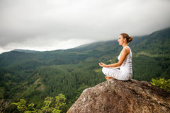 Woman is doing yoga exercises in mountains Royalty Free Stock Photography