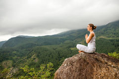 Woman is doing yoga exercises in mountains Stock Photos