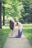 Woman doing yoga exercises outdoors in the city. Stock Photos