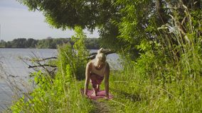Woman doing yoga exercises on the river bank. Attractive woman doing yoga exercises on the river bank under a tree stock footage
