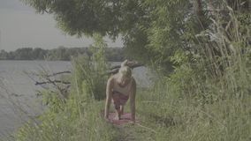 Woman doing yoga exercises on the river bank. Attractive woman doing yoga exercises on the river bank under a tree stock video footage