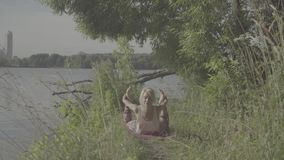Woman doing yoga exercises on the river bank. Attractive woman doing yoga exercises on the river bank under a tree stock video