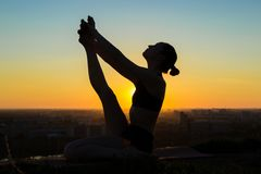 Woman doing yoga in floating boat pose in the park at sunset Stock Photos