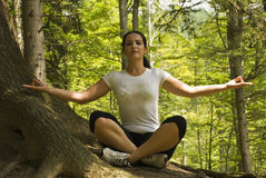 Woman doing yoga in forest at mountain. In nature in a sunny day and meditating with eyes closed and open hands,more photos with this model in royalty free stock photos