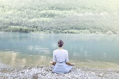 Woman doing yoga in front of a spectacular mountain lake Royalty Free Stock Photos