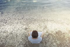 Woman doing yoga in front of a spectacular mountain lake Stock Photo