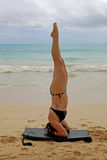 Woman Doing yoga headstand on beach. Young woman doing yoga on headstand beach in tropical location Royalty Free Stock Image
