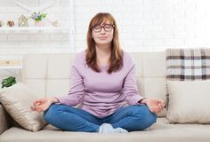 Woman doing yoga at home in the bedroom. Middle age female meditating indoors. yoga pose. lifestyle and menopause concept Royalty Free Stock Photography