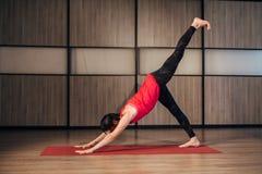 Woman doing yoga at home down dog split pose stock photos
