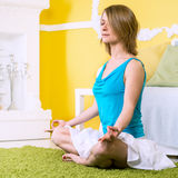 Woman doing yoga at home. Young caucasian woman doing yoga at home Stock Image