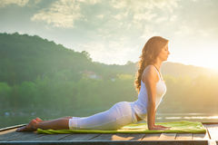 Woman doing yoga on the lake. Relaxing in nature stock photography