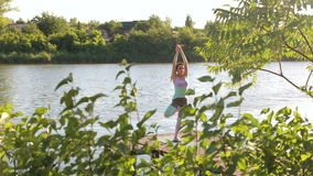 Woman doing yoga on the lake- relaxing in nature. stock video