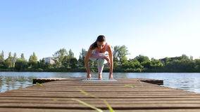 Woman doing yoga on the lake- relaxing in nature. stock footage