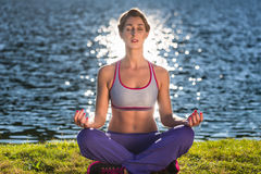 Woman doing yoga on lake. With the sun being mirrored in the water royalty free stock image