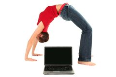 Woman doing yoga with laptop. Young woman performing yoga in front of a laptop Stock Image