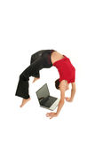 Woman doing yoga with laptop. Woman bending over backwards and using laptop Royalty Free Stock Photography