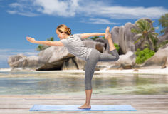 Woman doing yoga lord of the dance pose on beach Royalty Free Stock Photography