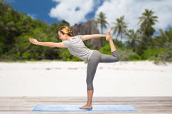 Woman doing yoga lord of the dance pose on beach Stock Photography