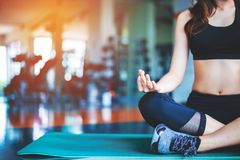 Woman doing yoga on mat at fitness gym. Sport and Exercise concept. Meditation and Fitness theme. Selective focus on hand stock photography
