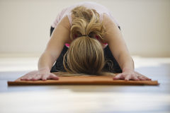Woman doing yoga on mat in studio Royalty Free Stock Photography
