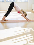 Woman doing yoga on mat in studio Royalty Free Stock Image