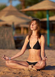Woman doing yoga meditation in lotus on the beach Stock Photography